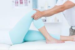 对腿按摩做的生理治疗师他的患者 免版税图库摄影