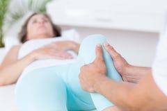 对腿按摩做的生理治疗师他的患者 免版税库存照片