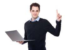 对膝上型计算机的商人用途和手指指向  免版税库存图片