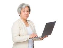 对膝上型计算机的老妇人用途 免版税库存图片