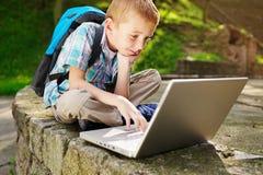 对膝上型计算机高兴的男孩 库存图片