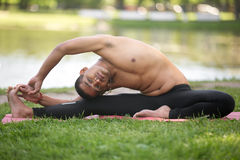 对膝盖瑜伽姿势的旋转的头 库存照片