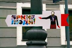 对节日`明亮的人`的尖,垂悬在一根路灯柱在Neglinnaya的城市天在莫斯科 免版税库存图片