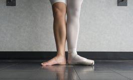 对芭蕾舞女演员、一条腿穿她的芭蕾拖鞋pointe鞋子在一只脚的和光秃一条的腿的双方 免版税库存图片