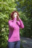 对花粉的深刻过敏:打喷嚏的妇女 免版税库存照片