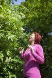 对花粉的深刻过敏:打喷嚏的妇女 图库摄影