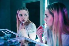 对药物的没有 应用她的有红色口红的年轻美女画象嘴唇在可卡因线附近在夜总会的 免版税图库摄影