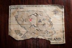 对葡萄酒伪造品的顶视图弄皱了在木桌上的珍宝地图 假与红十字的海盗手工制造地图作为宝物箱地方  库存图片