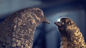 对葡萄酒白色鸽子由古铜和太阳背景制成 小雕象鸽子由金属制成 两个小雕象  免版税图库摄影