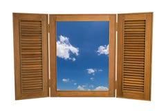 对蓝天看法的被打开的木窗口在白色Backg的 免版税库存图片