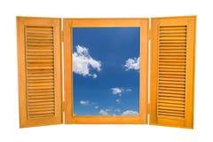 对蓝天看法的被打开的木窗口在白色Backg的 库存图片