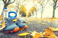 对蓝色体育鞋子浇灌,并且在一个树秋天胡同的一条道路放置的哑铃有槭树的留下-跑的exerc的辅助部件 库存图片