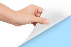 对蓝色的手转动的页 库存图片