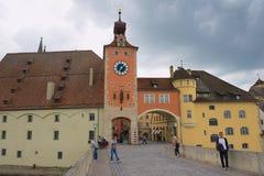 对街道的看法和老石桥梁在雷根斯堡,德国耸立 免版税库存图片