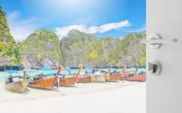 对被弄脏的长尾巴小船的被打开的白色门在白色沙子海滩 免版税库存图片