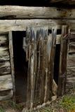 对被放弃的原木小屋的被风化的门 库存照片