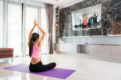 对训练瑜伽的亚洲夫人开始在客厅跟随在电视的教练 库存照片