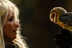 对谷仓猫头鹰的白肤金发的猎鹰训练术女孩注视 免版税库存图片
