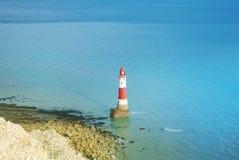 对象海滨顶头灯塔的鸟瞰图用英吉利海峡蓝色绿松石水在cli背景和白色白垩石头的  库存照片