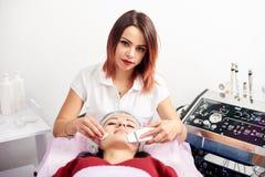 对超声波面部削皮做的美容师美容院的患者 免版税库存图片