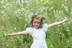 对边的小女孩手,从花的花圈 免版税库存照片