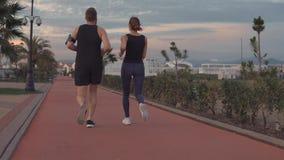 对运动的人和女孩在公园区域跑步在晚上,后面看法 影视素材