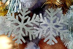 对银色在圣诞树的闪烁雪花形状的圣诞节装饰品 免版税库存图片