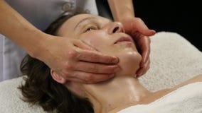 对防皱按摩做的女性医生客户 妇女享受在温泉saton的塑料面孔按摩 股票视频