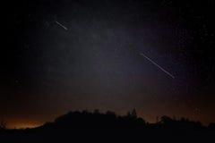 对飞星 流星雨和夜空与小山Sillouete  Persids, 8月流星 免版税库存照片