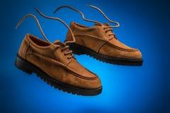 对飞行皮革麦子或棕色nubuck小船鞋子与飞行鞋带在蓝色背景 库存照片