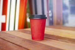 对饭菜外卖点的红色纸杯在咖啡馆之外的木地板上 水橇板立场后边在背景 免版税图库摄影