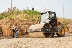对高速公路的压路机压缩的沙子 免版税库存照片
