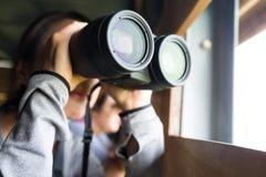 对鸟的监视人的双筒望远镜的亚洲妇女用途 免版税图库摄影