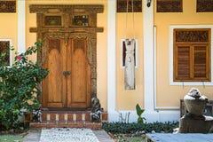 对黄色房子的入口有窗口的 与被雕刻的样式的老木门 导致一个锁着的门的石道路 免版税库存图片