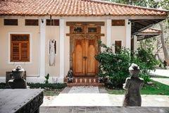 对黄色房子的入口 与被雕刻的样式的老木门 导致一个锁着的门的石道路 免版税图库摄影