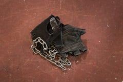 对黑体型和健身手套,有银色链子的辅助部件反对概略的红色背景 健身房设备 免版税库存照片