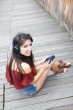 对年轻人的女孩听的音乐纵向 库存图片
