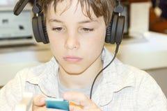对年轻人的男孩听的音乐纵向甜点 图库摄影