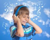 对年轻人的男孩耳机听的音乐 免版税图库摄影