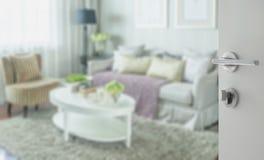 对经典客厅内部的被打开的白色门与沙发 库存图片