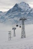 对移动滑雪者的缆车长平底船的看法上升在滑雪胜地在格林德瓦,瑞士 免版税库存照片