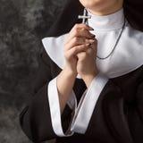 对负发怒和祈祷在墙壁的黑暗的背景的长袍的年轻尼姑 库存图片
