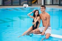 年轻对-坐由水池和做selfie照片的男人和妇女在有monopod的电话在豪华旅游胜地 免版税库存照片