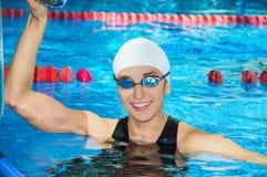 对水池的边的迷人的女孩游泳看照相机 免版税库存图片