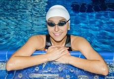 对水池的边的迷人的女孩游泳看照相机 库存照片