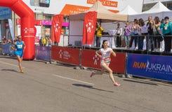 对终点线的妇女仓促在城市街道上的Interipe Dnipro半马拉松长跑期间 库存照片