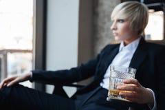 对负玻璃和坐在咖啡馆的美丽的白肤金发的女孩 图库摄影