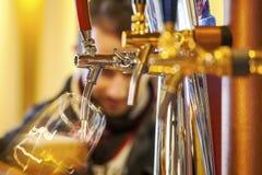 对玻璃的倾吐的啤酒 图库摄影