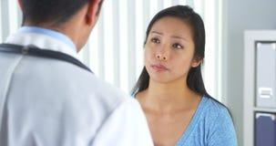 对医生的亚洲耐心描述的腕子痛苦 库存图片