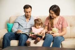 读对他们的女儿的三口之家 库存图片